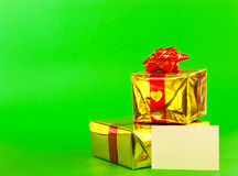 Two presents and blank card. Over green background Stock Images