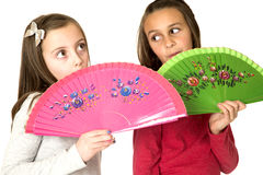 Two preteen girls with fun facial expressions behind oriental fa Royalty Free Stock Image