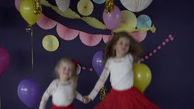 Two pretty baby girls sisters dancing and celebrating on birthday party. HD stock video footage