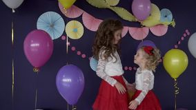 Two pretty baby girls sisters hugging and celebrating on birthday party. HD stock video footage