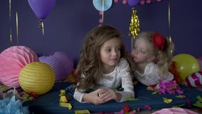 Two pretty baby girls sisters kissing and celebrating on birthday party stock video