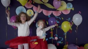 Two pretty baby girls sisters throwing bright confetti and celebrating birthday. Party stock footage