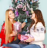Two pretty best friends girls opening Christmas presents near th Royalty Free Stock Photos