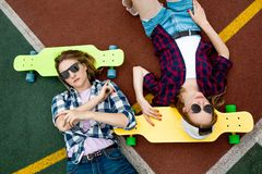 Two pretty blond girls wearing checkered shirts, caps and denim shorts are lying on the bright longboards on the royalty free stock photos