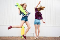 Two pretty blond girls wearing checkered shirts and denim shorts are jumping and dancing with bright longboards. Young. Girls are capering and having fun stock image