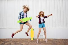 Two pretty blond girls wearing checkered shirts and denim shorts are jumping and dancing with bright longboards. Young stock photos