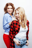 Two pretty blond woman having fun together on white background, mature mother and young teenage daughter, lifestyle Stock Photo