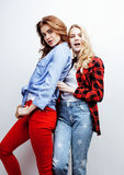 Two pretty blond woman having fun together on white background, mature mother and young teenage daughter, lifestyle Stock Photos