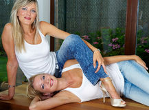 Two pretty blonde girls on the table Royalty Free Stock Photo