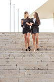 Two pretty businesswoman talking down the stairs Royalty Free Stock Photography