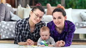 Two pretty casual smiling couple woman and little cute child posing looking at camera