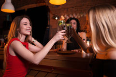 Two pretty Caucasian girls toasting drinking cocktails in pub celebrating birthday.  stock image