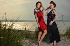 Two pretty Caucasian young fashionable women posing on the beach in luxury dresses. Horizontal photo royalty free stock images