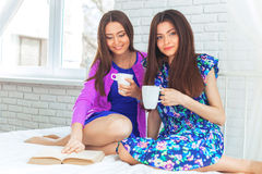 two pretty cheerful girls holds cup of coffee . Stock Photos