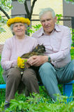 Two pretty elderly peoples. With cat on tehe hand Royalty Free Stock Photo