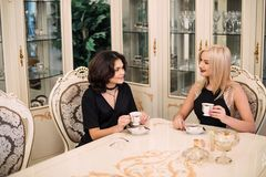 Two pretty, elegant girls talking about a cup of coffee sitting at a big table. Luxurious intranier in white tone Royalty Free Stock Images