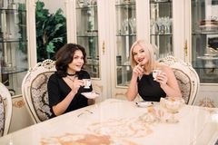 Two pretty, elegant girls talking about a cup of coffee sitting at a big table. Luxurious intranier in white tone Stock Photo