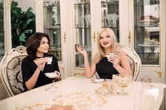 Two pretty, elegant girls talking about a cup of coffee sitting at a big table. Luxurious intranier in white tone Royalty Free Stock Photography