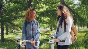 Two pretty female bicyclers with backpacks are talking standing in the park holding bikes. Pan shot of beautiful city. Two pretty female bicyclers friends with stock video footage