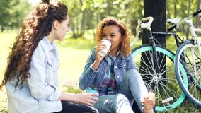 Two female cyclists are having rest drinking coffee sitting on lawn in park and chatting after riding bikes. Active. Two pretty female cyclists are having rest stock footage