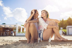 Two pretty female friends sitting together on beach laughing royalty free stock photography