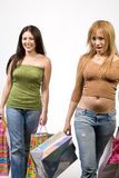 Two pretty female shoppers. Two young women smile as they stroll, with many shopping bags in their hands Stock Photo