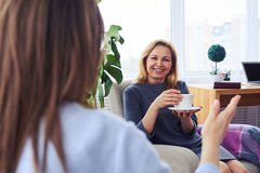 Two pretty females communicating while drinking coffee in living Stock Image