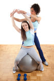 Two pretty fitness girls with ball and weights Royalty Free Stock Photography