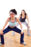 Two pretty fitness girls exercising together Royalty Free Stock Photos