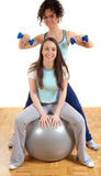 Two pretty fitness girls with weights and ball Stock Images