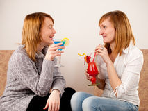 Two pretty friends celebrating. With colorful cocktails on white background Stock Images