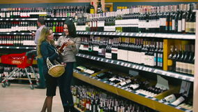 Two pretty friends choosing the wine in the supermarket. Beautiful girls standing near the stand with bottles of wine. Two friends are talking and choosing the stock video footage