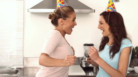 Two pretty friends dancing together in the kitchen stock video footage