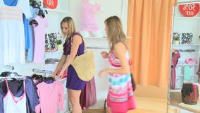 Two pretty friends are doing shooping. In a clothes store stock video footage