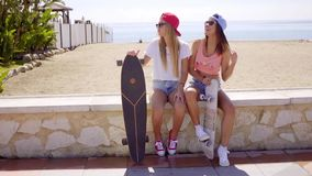 Two pretty friends hold skateboards on wall stock video footage