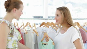 Two pretty friends looking through clothes rails Royalty Free Stock Images