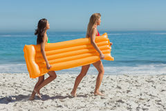 Two pretty friends running holding air mattress Royalty Free Stock Images