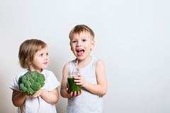 Two pretty fun kids with green smoothies and broccoli. Helthy an. Two pretty fun kids with green smoothies and broccoli over grey background. Helthy and clean stock image