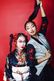 Two pretty geisha girls friends: modern asian woman and traditional wearing kimono posing cheerful on red background. Two pretty geisha girls friends: modern stock images