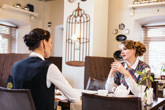Two pretty girl-friends talk in cafe Stock Image