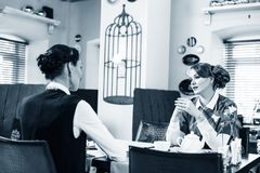 Two pretty girl-friends talk in cafe Royalty Free Stock Photo