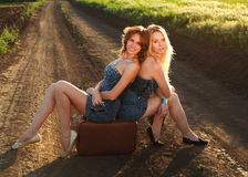 Two pretty girl, sitting on suitcase at countryside Royalty Free Stock Photo