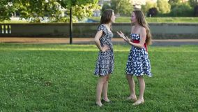 Two pretty girlfriend standing in a Park talking. Two pretty girlfriend standing in a Park talking, shot in full growth stock video