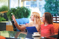 Two pretty girlfriends asking for waitress Royalty Free Stock Photo