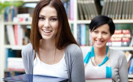 Two pretty girlfriends carry books Royalty Free Stock Photos