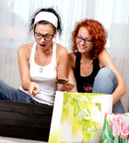Two pretty girls. Shopping over internet Royalty Free Stock Photo
