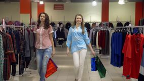 Two pretty girls with bags embrace and walk in shop stock footage