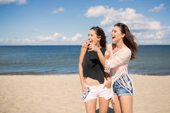 Two pretty girls on beach looking at something laughing. Portrait of two pretty girls on beach looking at something laughing Stock Image