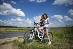 Two pretty girls on bike tour. On rock path Stock Images