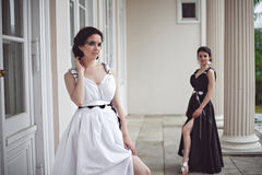 Two pretty girls in black and white long dresses Stock Image